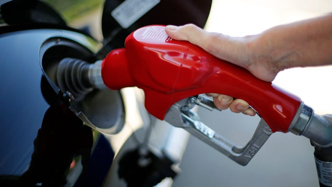 File photo taken in 2015 shows a woman filling up her car at a Costco gas station in Robinson Township, Pa.