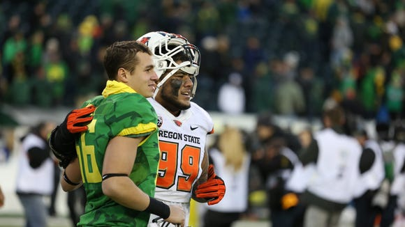 Oregon's Devin Melendez (left) and Oregon State's Kyle Peko pose for a picture after the Ducks defeat the Beavers 52-42 during Civil War Friday, Nov. 27, 2015, at Autzen Stadium in Eugene, Ore.