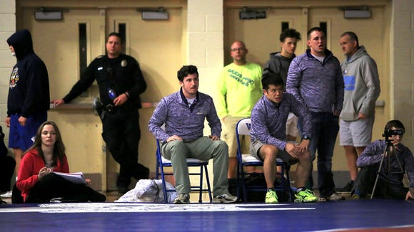 Heang Uy, seated in the right chair, has coached the North Henderson wrestling team for 15 seasons.