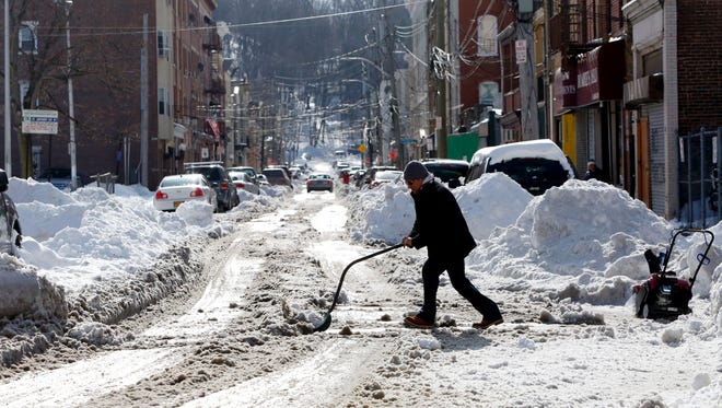 A man pushes snow onto the road as he cleans out a driveway in Yonkers Jan. 25, 2016. The city was hit with 20.5 inches of snow on Saturday. Schools were closed Monday as crews work to clear secondary and tertiary streets.