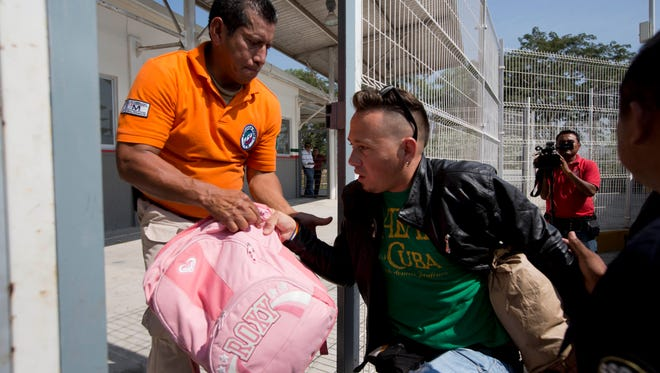 A Cuban migrant is helped with his luggage by a Mexican migration officer as he arrives to Ciudad Hidalgo, Mexico, on the border with Guatemala, on Jan. 13, 2016. After more than three months stranded in Costa Rica, 180 of the 8,000 Cuban migrants began their long-awaited trip north, toward the U.S. border.