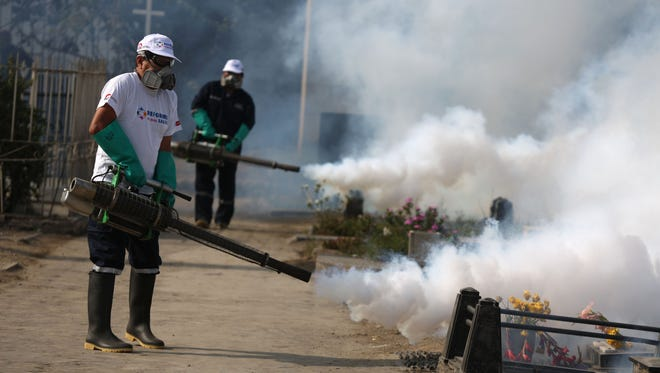 Health workers fumigate to prevent Dengue, Chikunguya and Zika virus, at El Angel cemetery, in Lima, Peru, Wednesday, Jan 20, 2016. A U.S. warning urging pregnant women to avoid travel to Latin American countries where the mosquito-borne virus is multiplying threatens to depress tourism to the region, one of its few bright spots at a time of deep economic pain. (AP Photo/Martin Mejia)