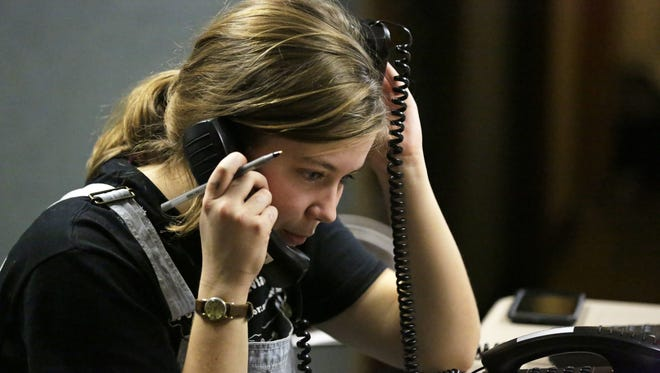 Willa Johnson works two phones as calls come in Sunday at the studios of WLFM on the Lawrence University campus during the Great Midwest Trivia Contest in Appleton.