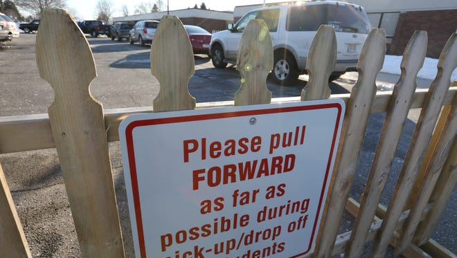 Signs at L.B. Clarke Middle School help direct the pick-up traffic after school on Thursday, Feb. 3, in Two Rivers. However, some parents think the signs do not improve the traffic congestion during pick-up and drop-off times.
