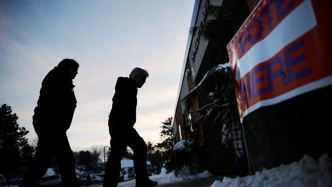 Voters walk in to a polling site at dawn to cast their ballots in the New Hampshire primary Tuesday, Feb. 9, 2016, in Nashua, N.H. (AP Photo/David Goldman)