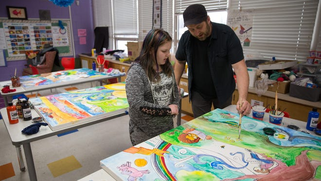Artist in residence Chad Elliot of Coon Rapids shows Lizzy Audes, 9, how to paint with watercolors Wednesday, Feb. 17, 2016, as Madison Elementary School 4th and 5th grade students create a triptych painting for the school in their art class.