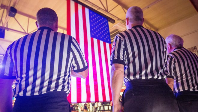 Referees stand for the national anthem at Wapahani High School during a home game.