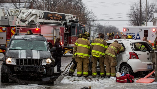 Members of the Port Huron Police and Fire Departments and Tri-Hospital EMS work the scene of an accident between an SUV and compact car Wednesday, Feb. 24 at the intersection of Erie and Rawlins Streets in Port Huron. Two adults and a child in the compact vehicle were transported to a local hospital.