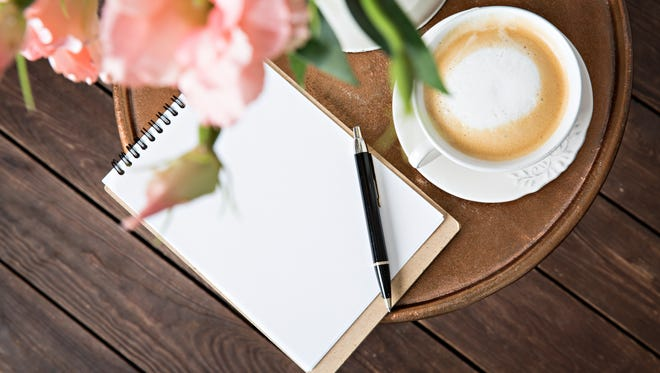 Notebook with a pen on the table next to coffe
