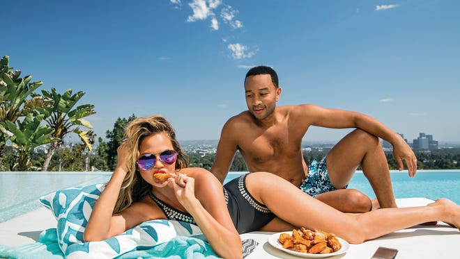 "Chrissy Teigen munches on ""John's Fried Chicken Wings with Spicy Honey Butter"" poolside, as hubby John Legend looks on. The recipe is included in her new cookbook, 'Cravings.'"