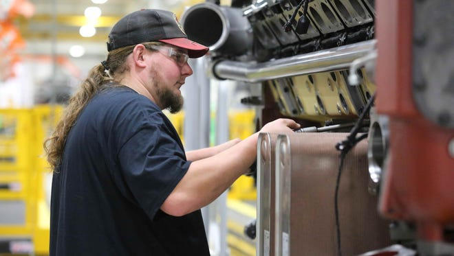 Matt Maschino work on water plumbing for an engine at the high-horsepower engine plant in Seymour operated by Cummins, Dec. 8, 2015.