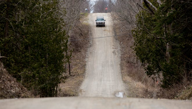 "A vehicle travels along Babcock Road, down a hill at Mill Creek known as ""Dead Man's Hill, in Worth Township. Officials want to widen the roadway to accommodate detour traffic when the M-25 bridge is closed for repairs."