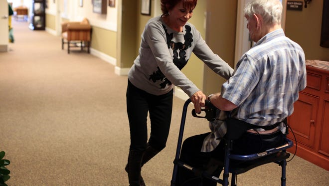 Gail Lansbury helps her husband Bruce Lansbury to his room after he got tired walking the halls at the Caleo Bay Alzheimer's Care Center in La Quinta on Tuesday, February 2, 2016.
