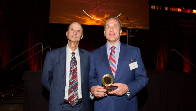 On the left, Gary Ostrander, vice president of research at Florida State University, stands with Partner of the Year Award winner Edward Mansouri.