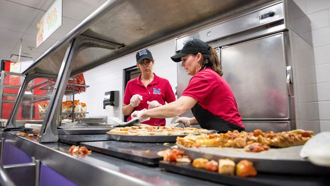 Cindy Beaty, right, helps get students their food on Monday afternoon inside Central's cafeteria. Beaty, a six year employee with the school has been adjusting as Chartwell took over cafeteria operations.