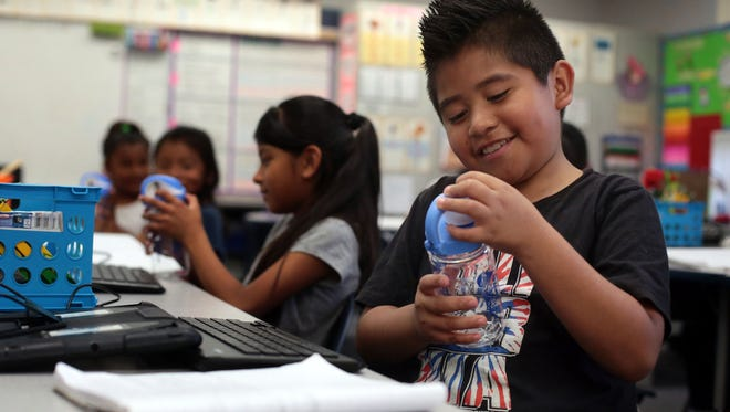 Third grader Gyovany Jimenez Basilio checks out his new water bottle, one of 700  given out to students at Las Palmitas Elementary School in Thermal Friday, April 8, 2016, by California Endowment's #Agua4All program for use with the 75 water filling station in the East Valley.