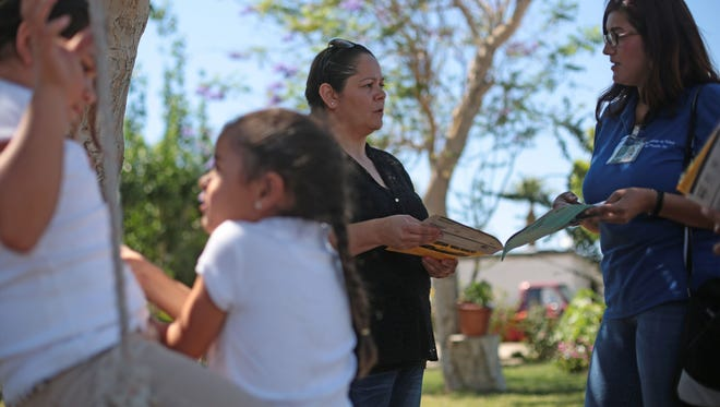 Yesenia Ortiz, with Clinicas de Salud talks to Maria Zazueta, 36, about Medi-Cal programs newly available to undocumented children as her daughters Georgina, 8, and Genesis, 5, play on a swing on Wednesday, April 13, 2016 at the Fred Young Farm Labor Camp in Indio.