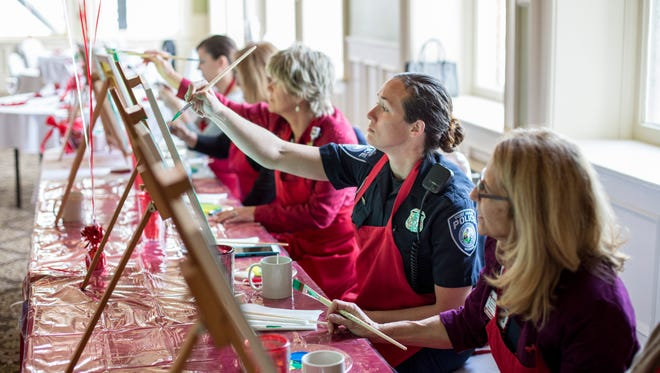Port Huron Police Officer Adrianne Mynsberge paints along with other community members during a therapeutic painting class for heart attack and stroke survivors Tuesday, April 19, 2016 at the Harrington Inn in Port Huron.