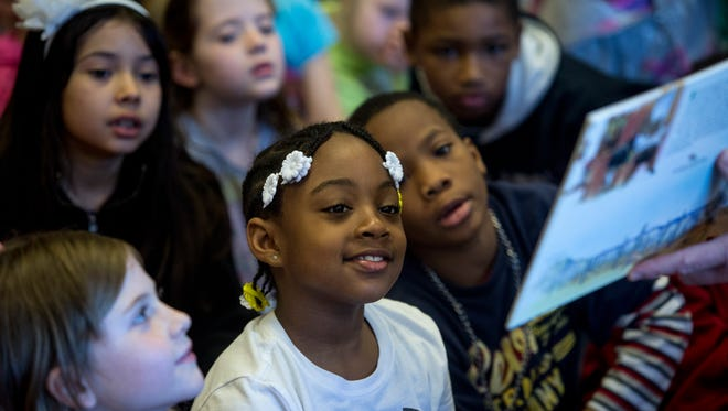 """Second-grade student Jamaica Taylor, 8, listens as Michigan Attorney General Bill Schuette reads the book """"The Three Little Javelinas"""" to students Wednesday, April 27, 2016 at Woodrow Wilson Elementary School in Port Huron."""