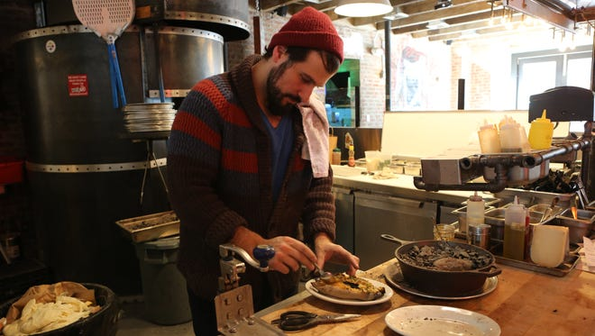 Chef David DiBari prepares sweet potato cooked in embers at The Parlor in Dobbs Ferry.