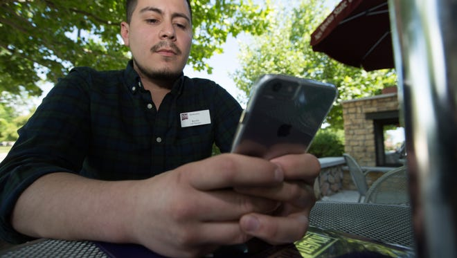 New Mexico State University student Kevin Lopez, 22, checks his phone during his lunch break at Barnes & Noble on campus.