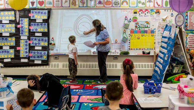 Kindergarten student Hayden Peters points out different parts to an egg next to teacher Miranda Landschoot Tuesday, May 10, 2016 at Keewahdin Elementary School in Fort Gratiot.