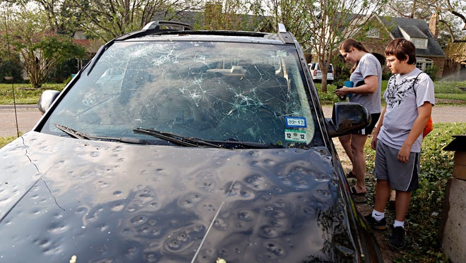 Nash Evans, right, 13, and his mother, Jennifer Evans, survey damage to their car in this 2012 file photo from Dallas