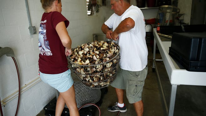 Kelly Kirk, left, and her father Damas Kirk lift 150-200 pounds of stone crabs into a mesh cylinder to be boiled on May 11 at Kirk Fish Company in Goodland on one of the final days of the 2016 stone-crab season.