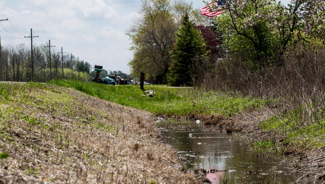 Water runs through a drainage ditch in front of homes Friday, May 13, 2016 in the 5800-5900 block of King Road in China Township. About 15 homes along the stretch of roadway have been leaking raw sewage into ditches for more than 10 years. The Department of Environment Quality issued a notice to the township regarding the issue in 2007.