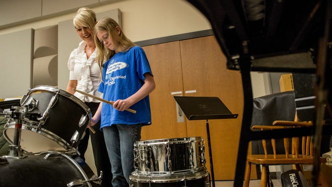 Instructor Robin O'Neill offers tips on how to play the drums to Bridget Fritz, 10, of Marysville, during Free College Day Saturday, May 21, 2016 at St. Clair County Community College in Port Huron.