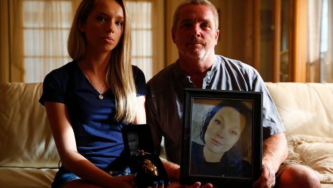 Allison King, 18, left, and Troy King, 50, are shown in portrait holding up the ashes and photo of Heather King, 21, May 18 at the King home in Bonita Springs. It's been a year since Heather King's body was found in a wooded area a short distance from the Days Inn on Tollgate Boulevard. She disappeared from the hotel on May 21 after leaving a friend's party.