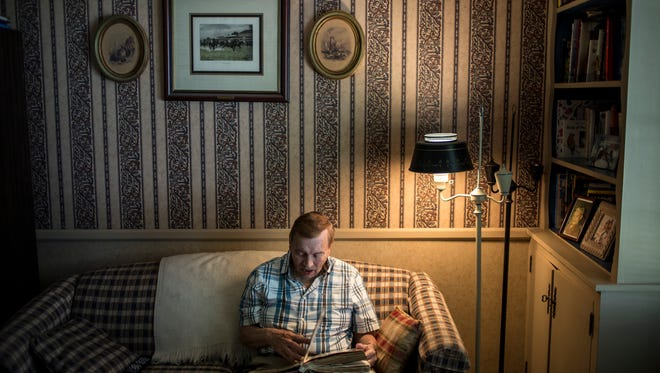 Frank Bacon flips through a scrap book with photographs and newspaper clippings of his time as a St. Clair County Commissioner Thursday, May 26, 2016 at his Port Huron home. Bacon has been an advocate for others' post-employment benefits since retiring as St. Clair County probate court administrator.