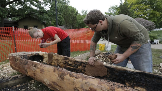 Sarah Fischer and Ian Poling, both students at the University of Wisconsin-Oshkosh, pack clay on the sides of the canoe to protect areas from burning. Seven students are working on the canoe in the manner Native Americans would have in the 17th century. The 16- foot-long canoe is made from white pine and will be completed next semester.