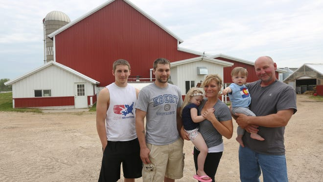 Ebert Farm owners Bob and Betsy Ebert pose for a portrait with their sons Elliott, left, and Austin, and two grandchildren Norah and Layne Schmatze, on their farm on Friday, May 27 in Reedsville. The Eberts established this farm in 1985 and started to provide milk for Organic Valley since 1994.