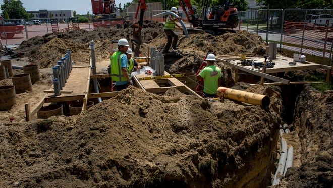 Contractors work on installing eight charging stations for Tesla Motors vehicles at the northwest corner of the DoubleTree by Hilton parking lot Friday, June 10, 2016 in Port Huron.