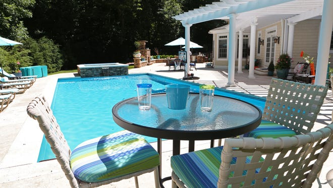 A new trend that home buyers are looking for is having an outdoor oasis that resembles the comfort of the indoors. Table and chairs by the pool in a Westchester backyard, June 14, 2016.