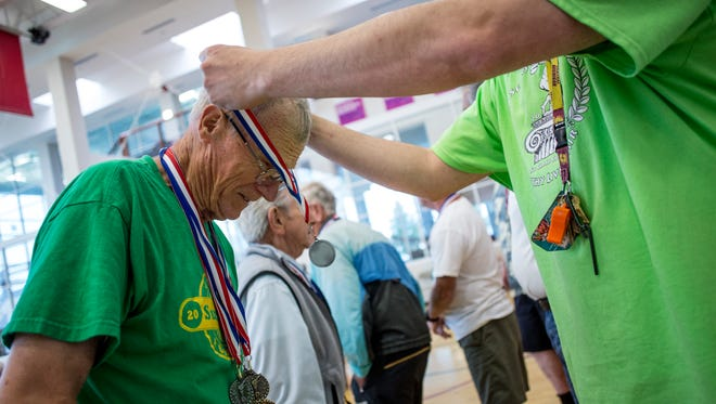 Harold Hyslop, of St. Clair Township, gets a medal for putting during the Senior Olympics Thursday, June 16, 2016 at the YMCA of the Blue Water Area in Port Huron.