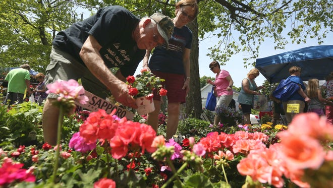 Manitowoc residents Ed and Christine Mahloch look for additional plants for their garden at the 26th Manitowoc Garden Fair at Washington Park on Saturday, June 11. Hundreds of people, including many from other cities, participated the fair.
