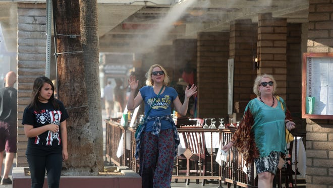Misters help keep people cool in Downtown Palm Springs Saturday, June 18, 2016. A heat wave is expected to hit the valley Sunday, sending temperatures as high as 121 degrees.