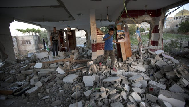 Palestinians inspect the house of Bashar Masalha?? after it was demolished by the Israeli army in the village of Hajja, near the West Bank city of Nablus, Tuesday, June 21, 2016. Troops demolished the home of Masalha who stabbed to death an American tourist and war veteran in an attack earlier this year. Israel says it carries out housing demolitions to deter future attacks. The Palestinians consider it a form of collective punishment. (AP Photo/Majdi Mohammed)
