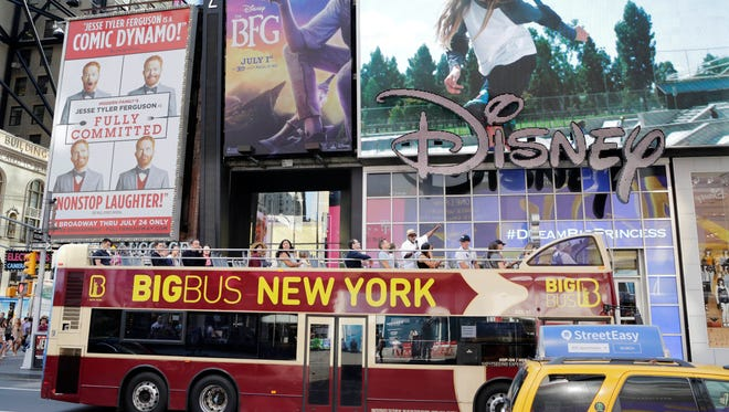 A double-decker tour bus passes through Times Square, Friday, in New York. Britain voted to leave the European Union after a bitterly divisive referendum campaign, toppling the government Friday, and sending global markets plunging. British tourists may find visits to New York more expensive as the pound weakens against the dollar.