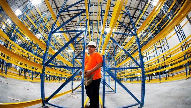 John Montoya, an employee of A1 Builders erects racking at the Restaurant Depot, a new warehouse off of U.S. 41 in South Fort Myers.  The business is a cash and carry food and supplies wholesale company.