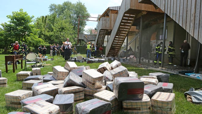 Firefighters removed boxes that were blocking an entryway as they battled an apartment building fire at 18 Calvert Drive that is being used as a warehouse July 18, 2016 in Monsey. Firefighters from Hillcrest, Spring Valley, Tallman, Thiells, Suffern and New City responded to assist Monsey.