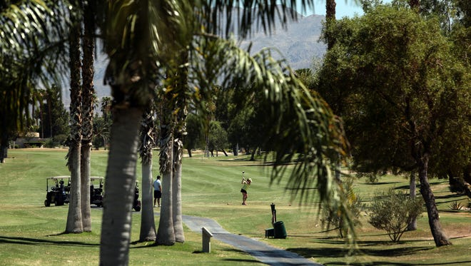 A golfer tees off at Desert Princess Country Club in Cathedral City. The golf course has made significant progress in removing grass and converting to desert landscaping. Water districts' records show, however, that Coachella Valley golf courses as a whole have fallen short of California's conservation goals during the past year.