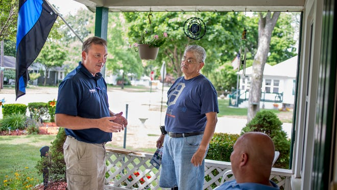 Phil Pavlov, of St. Clair Township, speaks with Leonard Coronado and Chuck Wilcox while going door-to-door to promote his campaign Thursday, July 28, 2016 on Hiscock Street in Port Huron. Pavlov, a republican, is running for Congress in Michigan's 10th Congressional District.