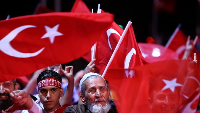 People wave Turkish flags as they take part in an anti coup rally at Taksim square in Istanbul, on July 26, 2016.