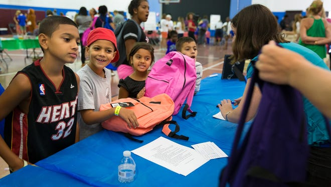 Geovanni Matias, 11, Joel Matias, 8, Sydney Matias, 7, and Donavin Matias, 9, left to right, select new backpacks for the upcoming school year at the third annual Back to School Bonanza at the Golden Gate Community Center on Saturday, July 30, 2016, in Golden Gate. The Friends of Foster Children Forever hosts the event benefiting around 350 foster children in Collier County where they receive free school supplies, haircuts, healthcare exams and other necessities.