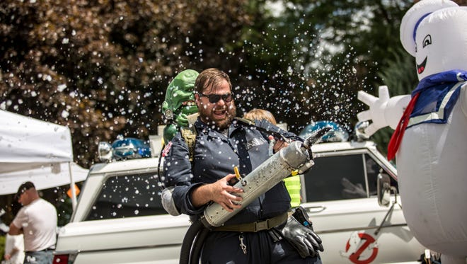 Andy Bisaha, of Detroit, sprays his slime gun while dressed as a Ghostbuster during the 2016 Marine City International Comic Con.
