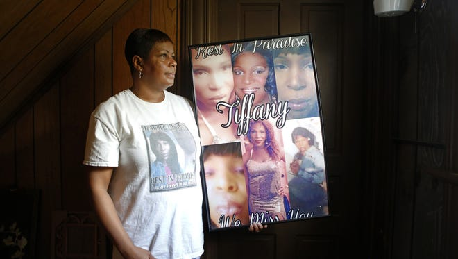 Temeka Edwards poses for a portrait in her home with a poster of her daughter, Tiffany, a transgender woman who was murdered in 2014.