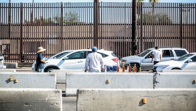 Hawkers on the Mexican side sell to cars waiting to cross into the United States at the Mexicali border crossing on Thursday, August 4, 2016. The town of Calexico on the US side is seen beyond the border fence.